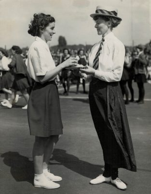 Miss 1901 (Miss R B Morton) offers Miss 1949 (Miss E Owen, England Captain) refreshment during the interlude between International matches being played at the GEC Sports Ground, Preston Road, London. | PA Reuter