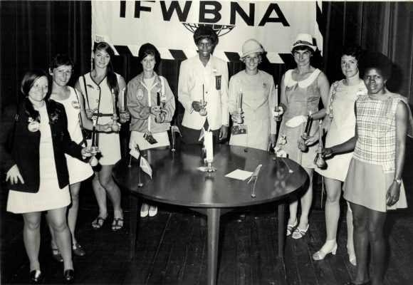 Candle lighting ceremony introduced by Rena Stratford, IFNA President.  Left to right - Marie Fairie (Scotland). Anne Lucas (Wales), Joan Harnett (New Zealand), Winnifred Russell (Bahamas), Miss Jean Gardner (Vice President). Miss Rena Stratford (President), Miss Leila Robinson, O.D. (Hon. Org. Secretary), Mrs Joyce Taylor, (Hon. Treasurer), Sonia Chronicle (Jamaica), Anne Miles (England), Gaye Walsh (Australia),Jill Finlay (Northern Ireland), Enid Browne (Trinidad and Tobago).
