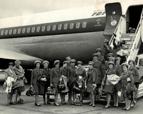 Prior to boarding:  From left to right (in uniform): Joyce Haines (Umpire), Rose Harris (Manager), Mary French (Coach), Phyllis Edwards, Pat Green, Liz Kelly, Eunice Charles, Marion Lofthouse (Captain), Isabel Martindale, Ann Davies, Miss Adelaide Brayford (Chairman), Miss Stratford (President): On the steps: Left: Janice Banister, Jackie Bowley, Joyce Wheeler Right: Judy Day, Anne Miles | London Press Photos