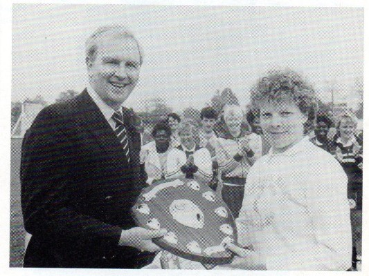 Debbie Ward, captain of Ducie, receiving the Challenge Shield from Les Priestly.