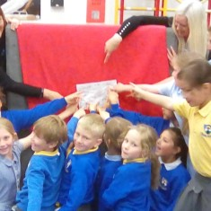 Sewing Club pointing to their names sewn on the back of the quilt