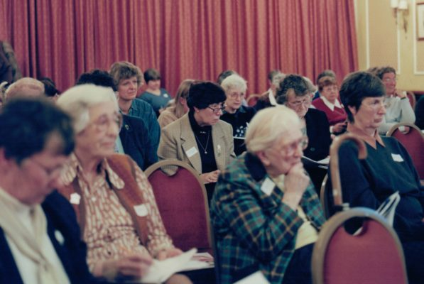 Members listening intently to the arguments including Sylvia Eastley, Mary Bulloch, and other stalwarts.