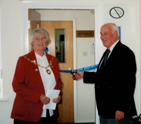 Mr Taylor with Jean Bourne, President cutting the ribbon to open the room dedicated to Pat Taylor at Hitchin.