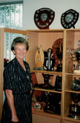Joan Mills in front of the trophy cabinet.