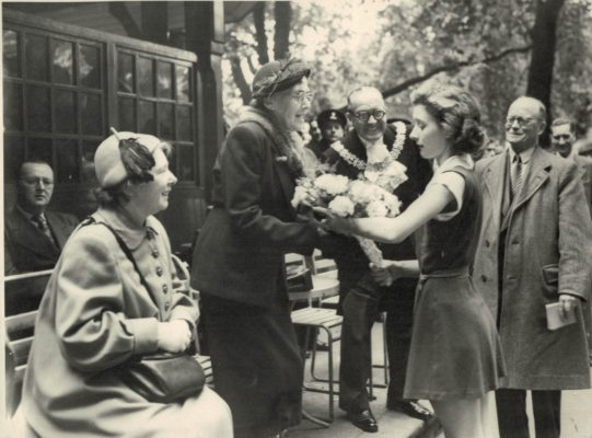 Elsie Sanders (sitting) AENA Secretary and is it Mary Bulloch with the presentation of flowers?