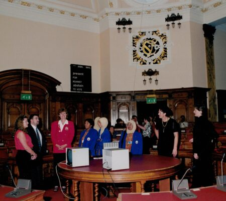 Civic reception in the Council Chamber, Cardiff.  England Manager Maggie Gartland third from the left, and Jan Teesdale, second from the right and Chris Burton from New Zealand.  In the background is Sheelagh Redpath (black and white blouse) and Mary French, seated.