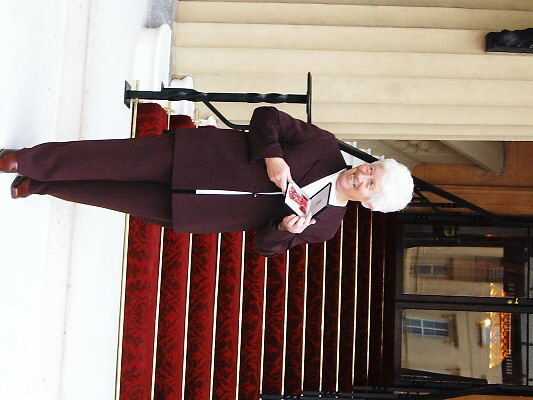 Gina in the courtyard of Buckingham Palace with her MBE from the Queen