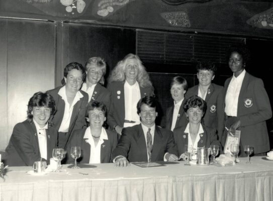 1987 Colin Moynihan, Minister of Sport invited the England Squad to a lunch at the Royal Variety Club, London.  Front row left to right:  Kendra Lowe, Sue Keal, Colin Moynihan, Jillean Hipsey.  Back row left to right: Linda Dyer, Maggie Jackson, Heather Crouch, Colette Thompson, Sheila Edwards, Jess Parkes | Professional Photographic Services