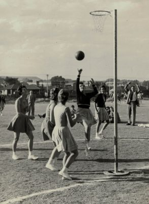 Nora Ashworth, Southern Transvaal, making a running shot at goal during a match in South Africa between Southern Transvaal and Northern Transvaal.  Note the dusty grass court, a surface indigenous to South Africa at the time. | Syd Ziegler